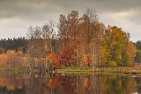 Fisherman on the lake. Autumn colors on the Stone Lake, Poland
