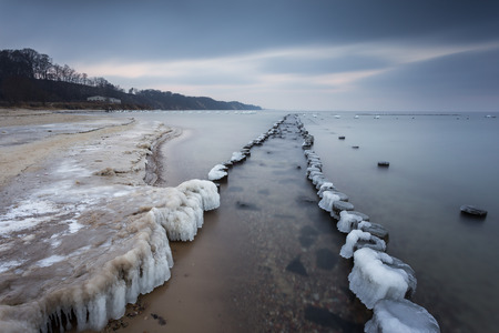 Winter landscape at the sea. Frozen wooden breakwaters line to the world war II torpedo platform at Baltic Sea. Morning at Babie Doly, Poland. Long exposure photo.