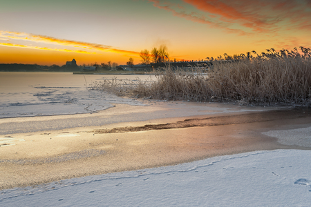 Winter landscape at frozen bay of Puck. Warm light of sunrise early morning. Poland. Stock Photo