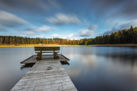 Small woody fishing pier at the lake. Moody colors of sunset. Poland.
