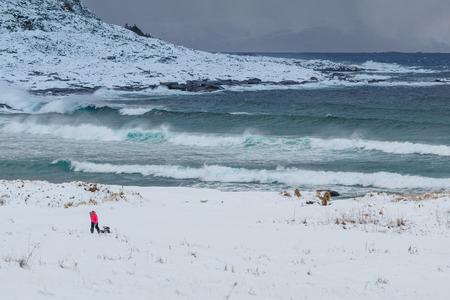 Child with sledge. Winter landscape at Godoya Island near Alesund, Norway Stock Photo