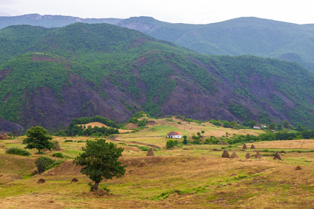 Scenic landscape view in Albanian mountain with small village and hay shocks. Stock Photo