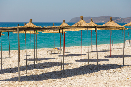 Umbrellas on the Borsh Beach in Albania. Stony beach on the Adriatic Sea.