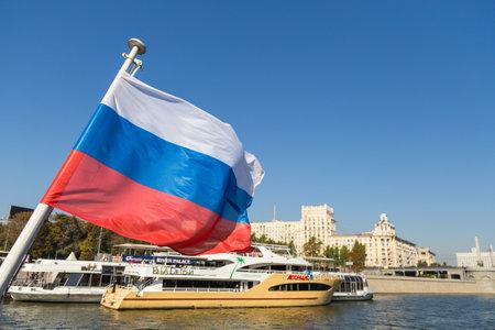 Moskau, Russland - 21. September 2014: Russische Flagge auf der Moskwa im Hintergrund, moderne Gebäude an den Ufern.