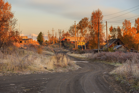 Frosty morning in Kozyriewsk, small village in Kamchatka Peninsula. Sandy road and poor wooden buildings and fence. Russia. 版權商用圖片