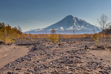 Mount Ostry Tolbachik, the highest point of volcanic complex on the Kamchatka Peninsula in the far east of Russia. Black, volcanic sand in the first plan.