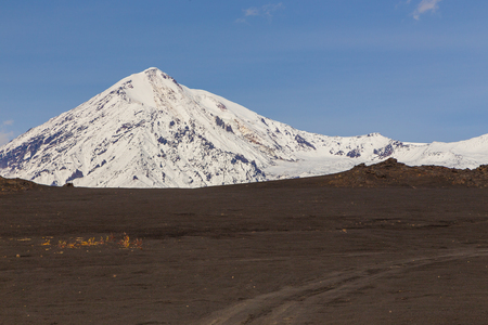 Snow- capped Mount Ostry Tolbachik, the highest point of volcanic complex on the Kamchatka Peninsula in the far east of Russia. Black, volcanic sand in the first plan. Stock Photo