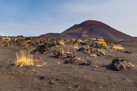 Unnamed, extinct volcano on the Kamchatka Peninsula in the far east of Russia. Black, volcanic sand and yellow shrubs in the first plan.