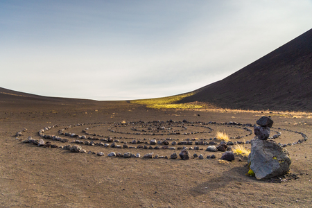 Stone circle laid out on darker volcanic soil on the Kamchatka Peninsula in the far east of Russia. Black, volcanic stone and yellow shrubs and green moss. Stock Photo