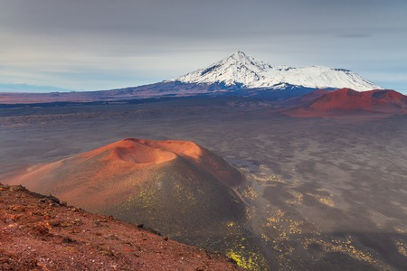 Snow- capped Mount Ostry Tolbachik, the highest point of volcanic complex on the Kamchatka Peninsula in the far east of Russia. Unnamed, extinct volcano in the first plan.