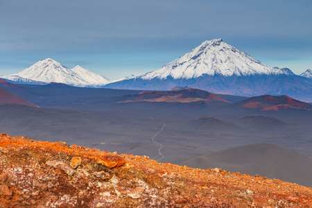 Snow- capped Mount Bolshaya Udina, volcanic massive, one of the volcanic complex on the Kamchatka Peninsula in the far east of Russia. Black sand in the first plan. Foto de archivo