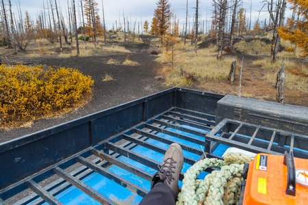 Travel on the roof of a truck. leg in a trapper boots. Equipment off road expedition, rope and yellow box. Around dead forest with withered trees. Kamchatka Peninsula, Russia.