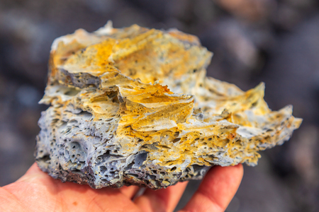 Fragment of fresh lava in hand, volcanic area Mount Ostry Tolbachik. Kamchatka Peninsula in the far east of Russia.