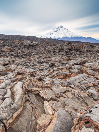 Snow- capped Mount Bolshaya Udina, volcanic massive, one of the volcanic complex on the Kamchatka Peninsula in the far east of Russia. Fresh lava field in the first plan. Stock Photo