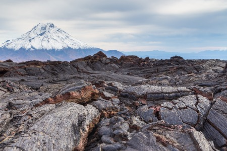 Snow- capped Mount Bolshaya Udina, volcanic massive, one of the volcanic complex on the Kamchatka Peninsula in the far east of Russia. Fresh lava field in the first plan. Reklamní fotografie