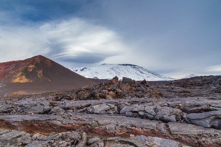 Snow- capped Mount Ostry Tolbachik, the highest point of volcanic complex on the Kamchatka Peninsula in the far east of Russia. Fresh lava field in the first plan.