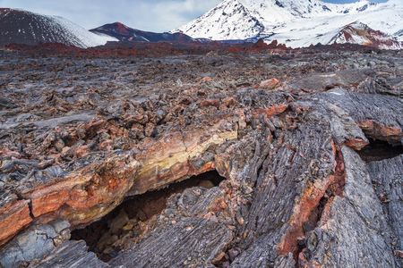 Bizarre formation on fresh lava field. Snow- capped mountain in the background. Volcanic complex on Kamchatka Peninsula in the far east of Russia.