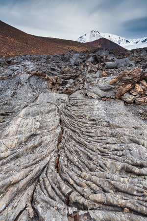 Bizarre formation on fresh lava field. Snow- capped Mount Ostry Tolbachik, the highest point of volcanic complex in the background. Kamchatka Peninsula in the far east of Russia.