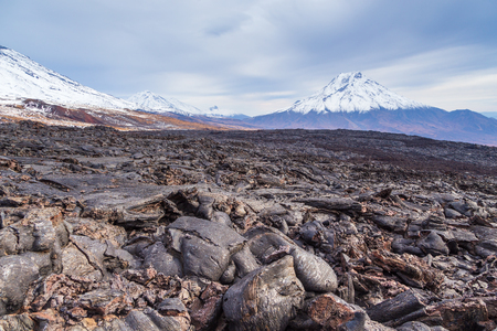 Bizarre formation on fresh lava field. Snow- capped Mount Bolshaya Udina in the background. Volcanic complex on Kamchatka Peninsula in the far east of Russia. Imagens