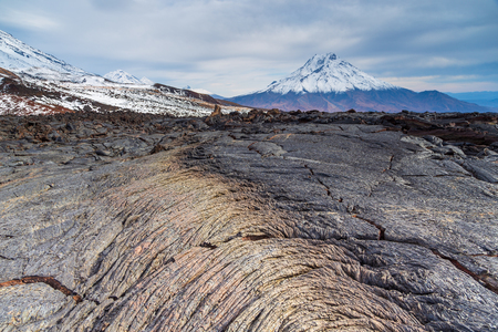 Bizarre formation on fresh lava field. Snow- capped Mount Bolshaya Udina in the background. Volcanic complex on Kamchatka Peninsula in the far east of Russia.