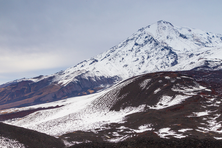 Snow- capped Mount Ostry Tolbachik, volcanic massive, one of the volcanic complex on the Kamchatka Peninsula in the far east of Russia. Fresh lava field in the first plan.