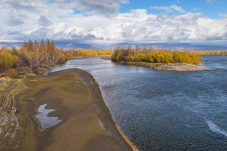 View of the Kamchatka River. Forest in autumn colors, mountain in the background. Kamchatka Peninsula, Russia