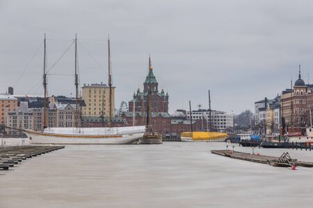 Helsinki, Finland- 28 February 2015: View of the Uspenski Cathedral set upon a hillside on the Katajanokka peninsula overlooking the city. frozen bay with piers and a yacht in the first plan. 報道画像