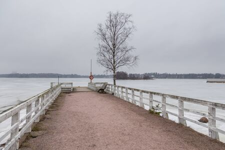 Small pier at beach with red lifebuoy in Seurasaari island. Baltic coastline. Winter landscape in Finland.