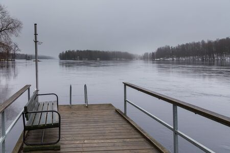 Small pier at beach on Lake Ruotsalainen, bench on a pier. Winter landscape, Heinola, Finland.