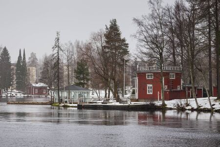 Small,red, wooden house on the bank Ruotsalainen Lake. Winter landscape, Heinola, Finland.