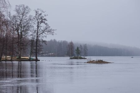View of the Ruotsalainen Lake in winter scenery. Small, rocky islands, boats pulled ashore, Heinola, Finland.