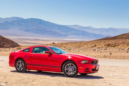 Death Valley, California USA- 02 June 2015: Red Ford Mustang on the Artist Dr. Desert salt pan in the background.