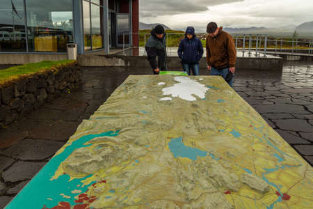 Thingvellir, Iceland- 22 August 2015: Tourists watching a model of Iceland in front of the Visitor Center in National Park.