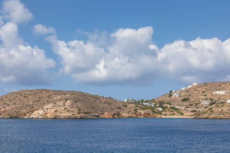 View of the bay leading to the port of Chora. Hills with white traditional buildings in the background. Ios Island, Greece.