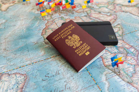 Poland, Gdansk - 19 April 2020: Polish passport and notebook on a colored world map with embedded flags. Travel or tourism concept. Editorial