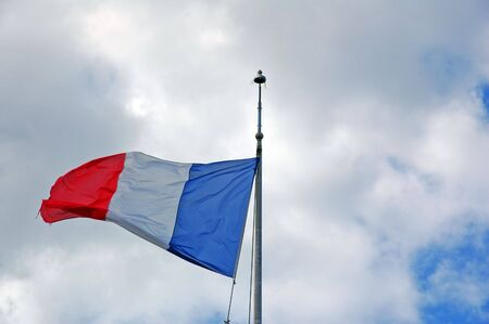 france flag in blue sky with clouds