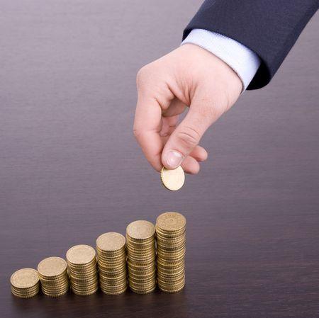 Mano mettere moneta scala soldi sulla scrivania di legno