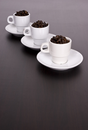 3 white cups with coffee beans on brown table Stock Photo