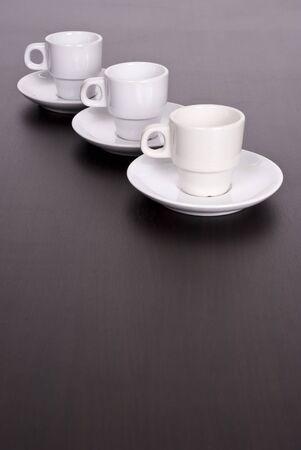3 tazze di caff� bianco sul tavolo marrone