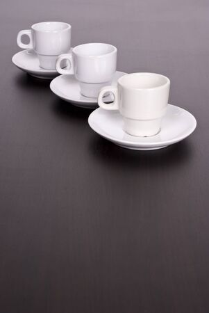 3 white coffee cups on brown table Stock Photo