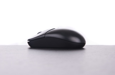 Wireless black computer mouse over table with white background Stock Photo