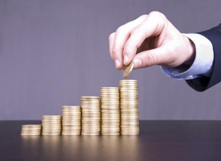 Maschio mano caucasica accatastamento monete in una scala