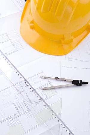 Blueprint architetturali con l'elmetto protettivo, riga e compasso