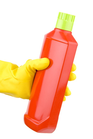 Hand with yellow glove holding bottle of detergent Stock Photo