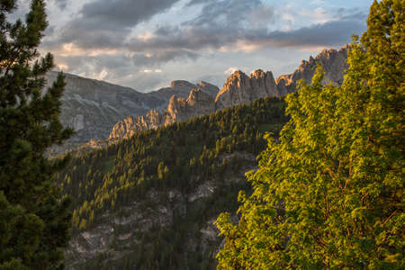 Sunset coloring the Cirspitzen in the Dolomites above Val Gardena in South Tirol. Cir Mountain in the middle of the Dolomites, scneic view between Trees