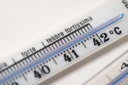 Clinical thermometer in analog form. Mercury thermometer on white background with italian writing. High fever. Fourty two degrees of fever