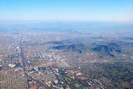 Aerial view of Phoenix city with buildings and CamelBack mountain in Arizona. photo