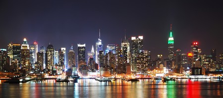 hudson: New York City night skyline panorama over Hudson river with boat and skyscraper and colorful reflections.
