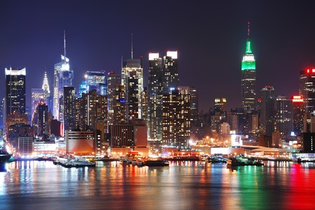 Empire State Building, New York City with Manhattan Skyline at night panorama over Hudson River with reflection.