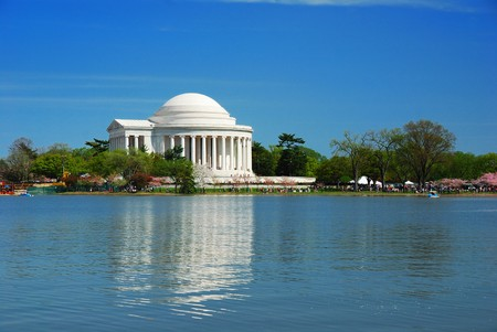 Thomas Jefferson national memorial with cherry blossom over lake with reflection in Washington DC.